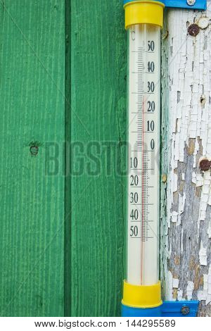 Thermometer attached on the wall shows the temperature of the air 29°С