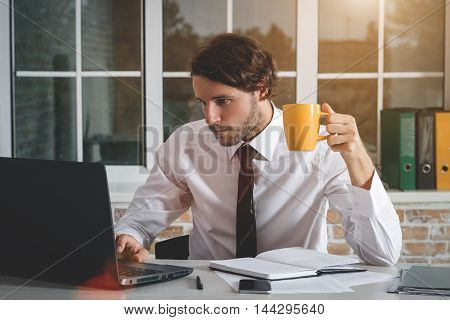 Handsome Young Businessman Sitting At His Workplace Looking At His Laptop And Drinking Tea. Business Theme