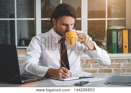 Handsome Young Businessman Sitting At His Workplace Looking At His Notebook And Drinking Tea. Business Theme