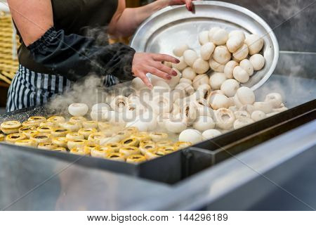 A cook cooking mushrooms in a kitchen.