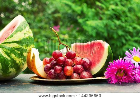 cut slices of ripe yellow melon watermelon a bunch of grapes and flowers asters on a table with natural green background. shallow depth of field