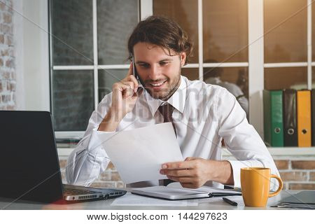 Smiling Handsome Young Businessman Sitting At His Workplace Holding A Paper And Talking On The Smartphone. Business Theme