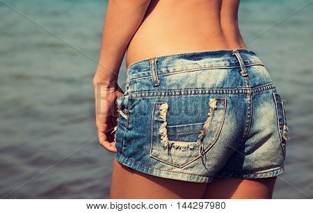 Sexy Tanned Woman Back In Fashion Blue Shorts On Blue Sea Background