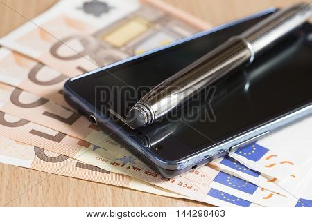 Mobile phone pen and euro banknotes close up