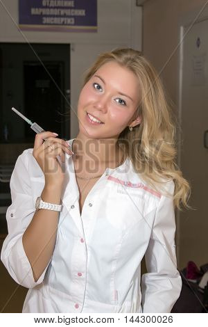 The blonde the nurse in a white dressing gown with a syringe