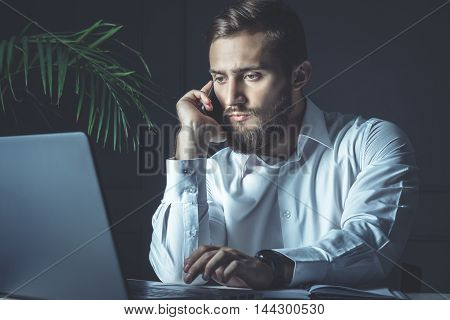 Handsome Young Bearded Businessman Sitting At His Workplace Looking At His Laptop And Talking At Smartphone. Business Theme
