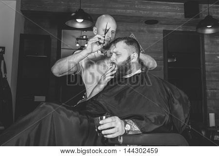 Serious Bearded Man Getting Haircut By Barber And Holding A Glass Of Whiskey While Sitting In Chair At Barbershop And Smoke Cigarettes. Barbershop Theme