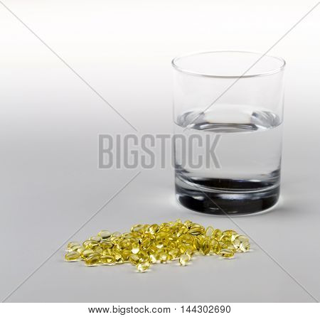 Vitamin E Pills Capsules White Background Isolated with glass of water tight close view crop