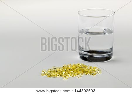 Vitamin E Pills Capsules White Background Isolated with glass of water wide crop view