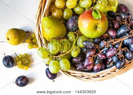 The big basket with autumn fruit on white wooden table