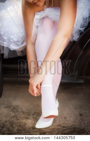 bride puts on shoes while sitting in the car. beautiful girl in a wedding dress sits on the car seat and buttons ankle strap with high heels