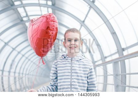 red heart balloon and happy boy. cheerful child with a gift on February 14. Valentine's day, day of lovers. the concept of happy love