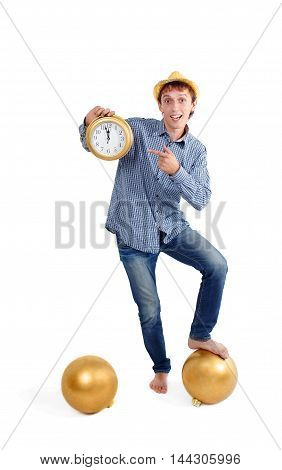 the Happy New Year is approaching. the concept of approach of the New Year. cheerful guy in a gold hat showing midnight on the clock. at his feet lie the huge Christmas tree balls. isolated on white background