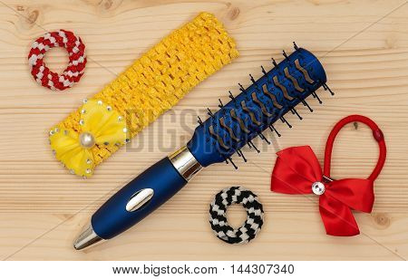 New hairbrush with accessories over wooden surface