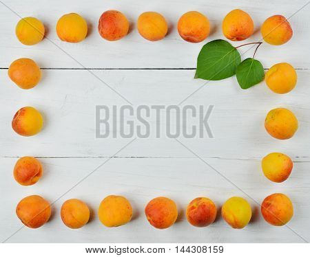 The decor of ripe apricots with leaves. Top view. Frame. autumn. harvest. Summer. Gardening. Hobby. Fruit.