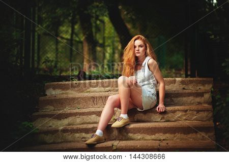 Portrait of a beautiful red-haired girl at sunset