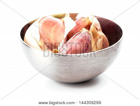 Cloves of unpeeled garlic in little bowl isolated over white background