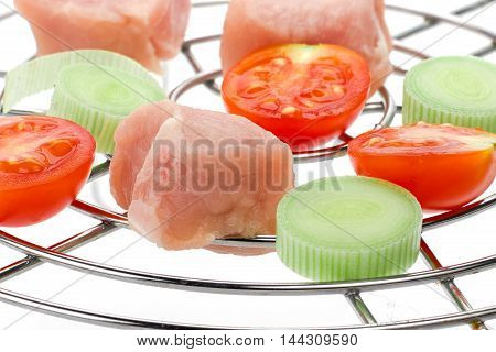 Piece of raw pork meat and vegetables on grill rack isolated over white background