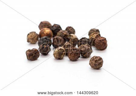 Whole black pepper grains isolated over white background