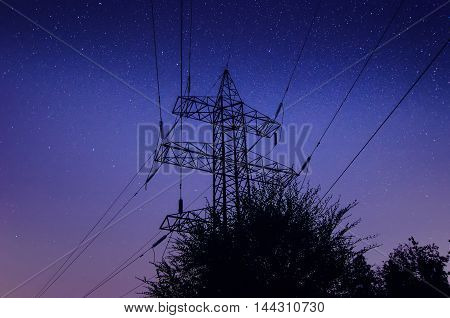 Power lines and tower against night sky with stars and milky way galaxy