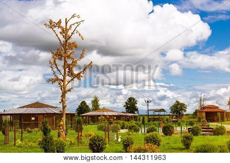 Amber tree with decorative leaves made of amber stands in landscaped Park with green bushes and bird cages.