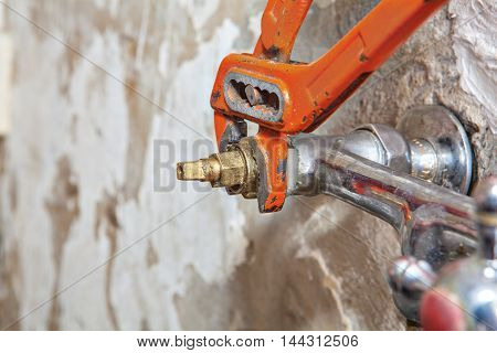 Two handle kitchen faucet repair remove water tap valve replacing worn valve seat using red plumber pliers close-up.