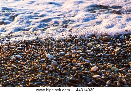 Foam sea wave rushes at pebble seashore shore of beach is covered in glittering sun stones. Stone background with texture of pebbles. Sochi Krasnodarskiy kray Russia