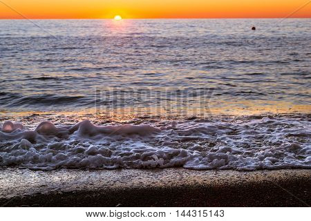 Foam Sea Wave Rushes Onto Seashore At Sunset
