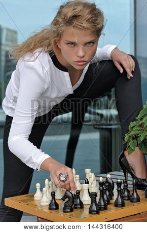 Fashion Model Bent Over A Chessboard
