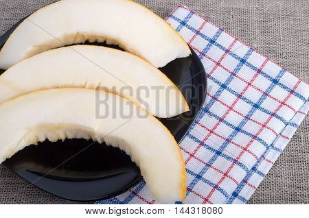 Sweet Yellow Melon Slices On A Black Plate