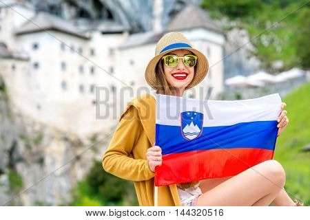 Young female traveler holding slovenian flag near Predjama castle. This castle is a famous tourist attraction and a travel destination in Slovenia