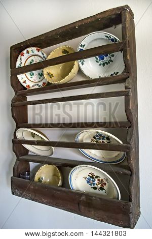 Old plates on a shelf on the wall