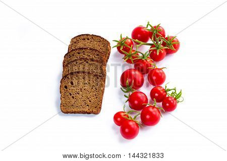 Composition of black bread slices and bunch of cherry tomatoes