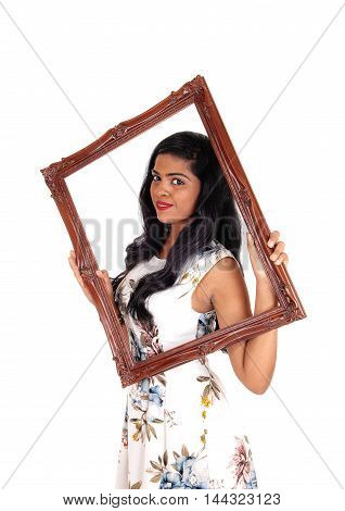 A beautiful Indian woman with long black hair holding up a picture frame and looking trough isolated for white background.