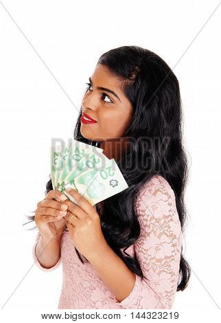 A beautiful young Indian woman holding sine Canadian money looking up and dreaming isolated for white background.