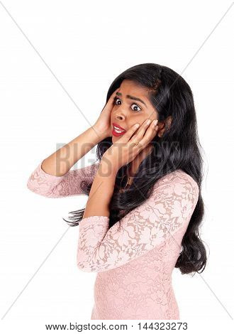 A lovely young Indian woman holding both hands on her face and looking very scared isolated for white background.