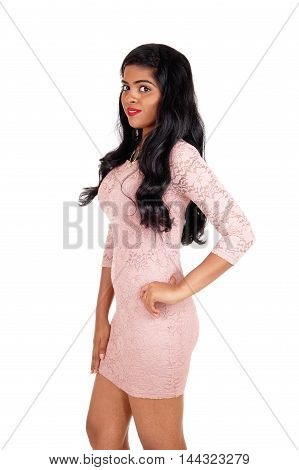 A very beautiful young Indian woman standing in a beige tight dress and long black hair isolated for white background.