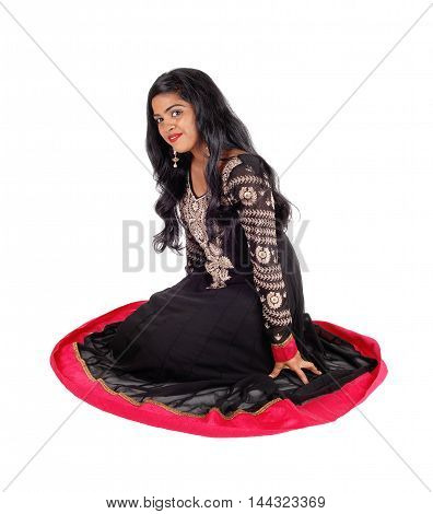 A beautiful Indian woman in a native black dress and long black hair sitting on the floor isolated for white background.