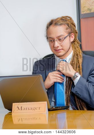 Handsome man with dreads and business suit sitting by desk, adjusting tie while looking at laptop, young manager concept.