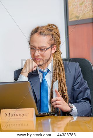 Handsome man with dreads and business suit sitting by desk, holding mobile phone while looking at laptop, young manager concept.