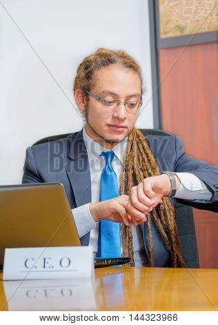 Handsome man with dreads and business suit sitting by desk looking at wrist watch, young manager concept.