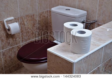 Two rolls of white toilet paper in the background toilet bowl with a wooden toilet seat