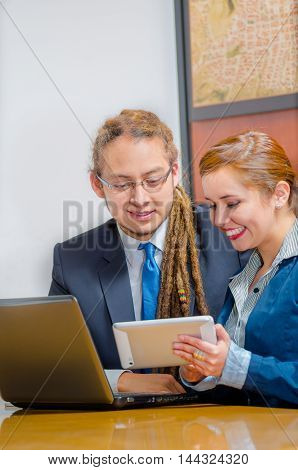 Handsome young man wearing formal suit sitting down with pretty female co-worker looking at screen and discussing between each other, office manager concept.