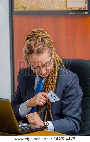 Handsome man with dreads, glasses and business suit sitting by desk placing a paper which has the word ceo written on it in his pocket, young manager concept.