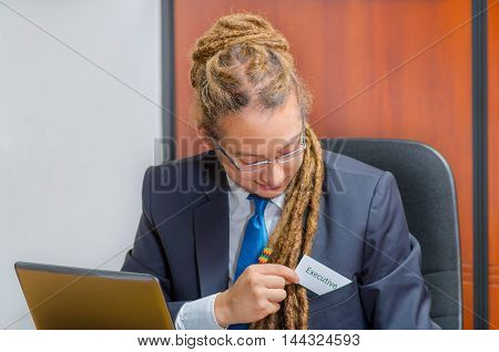 Handsome man with dreads, glasses and business suit sitting by desk placing a paper which has the word executive written on it in his pocket, young manager concept.