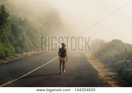 young woman walks into a lot of haze on a street