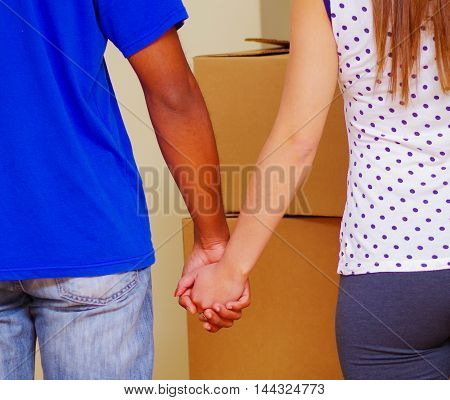 Interracial couple holding hands, seen from behind with stacked boxes in background, moving in concept.
