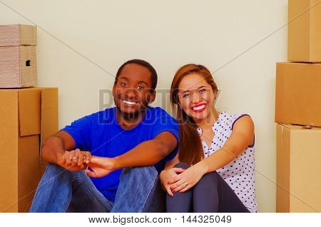 Charming interracial couple smiling to camera, friendly interacting while sitting between cardboard boxes, moving in concept.