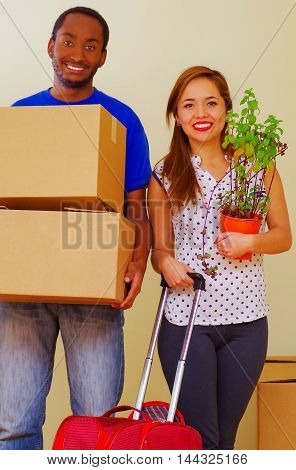 Charming interracial couple holding cardboard boxes and plant while smiling to camera, moving in concept.