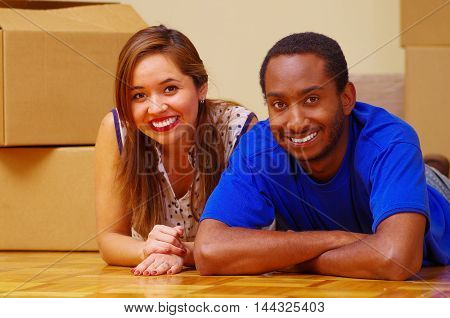 Charming interracial couple smiling to camera, friendly interacting while lying between cardboard boxes, moving in concept.